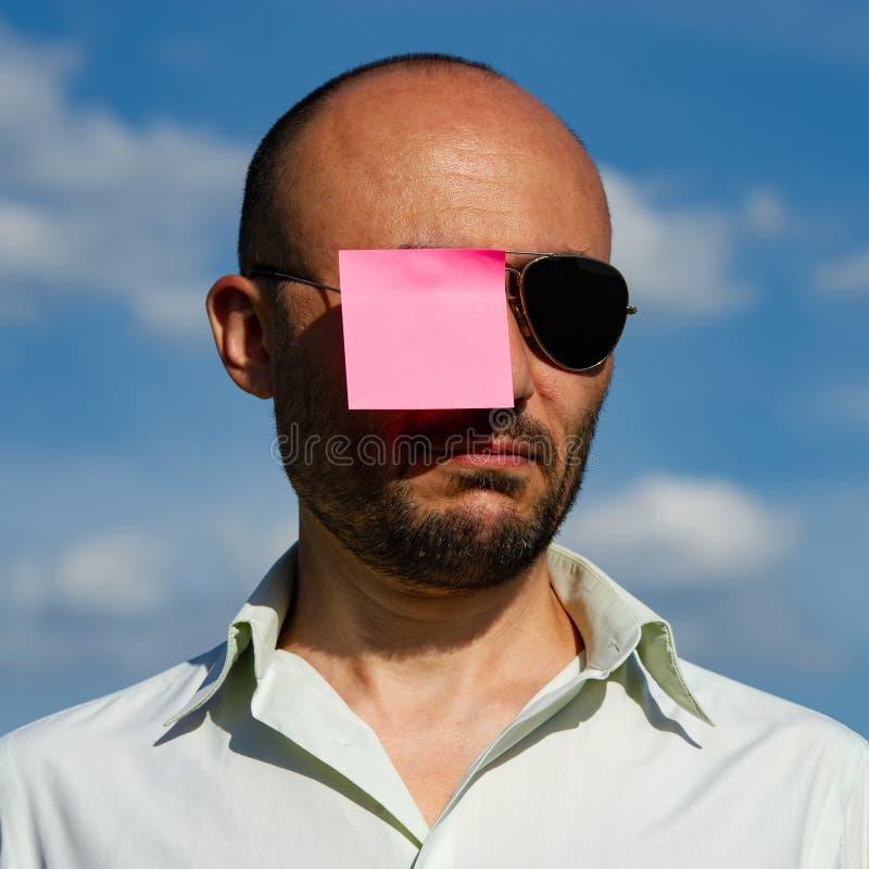 一个商人的概念性画象在被黏贴的现代太阳镜的 免版税库存照片