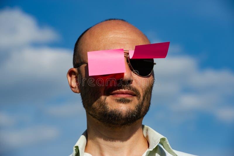 一个商人的概念性画象在被黏贴的现代太阳镜的 免版税库存图片