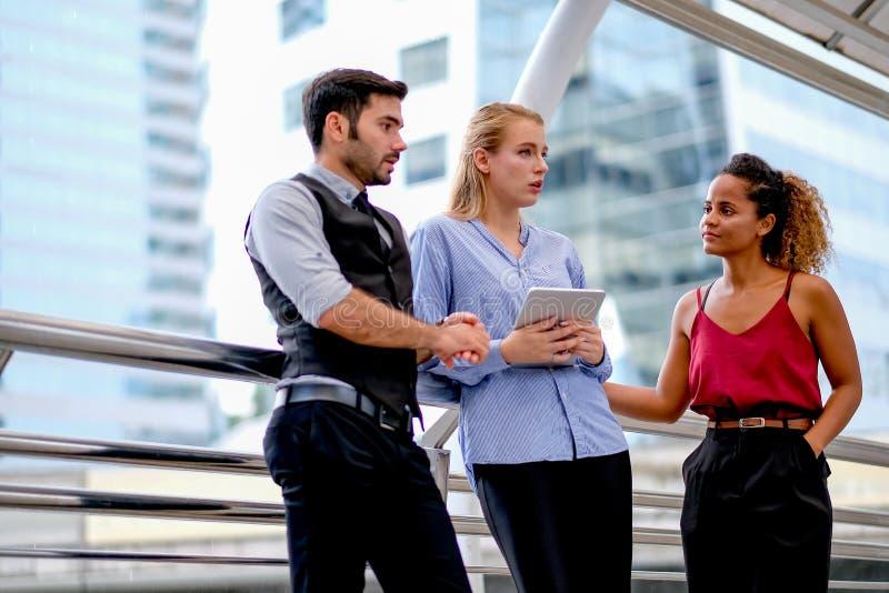 一个商人谈论关于工作与他的队,两名妇女与举行的一名混合的族种棕褐色的皮肤和白白种人妇女 库存图片
