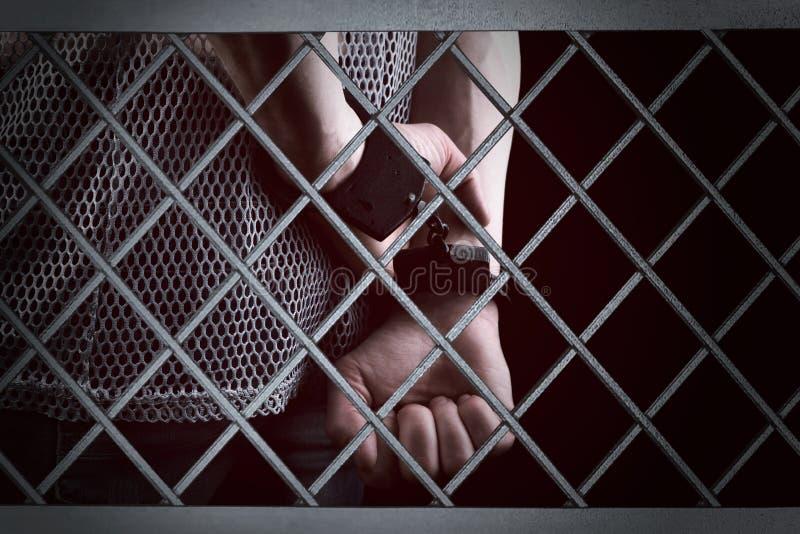 一个囚犯的手在铁棍后的在监狱牢房 免版税库存图片