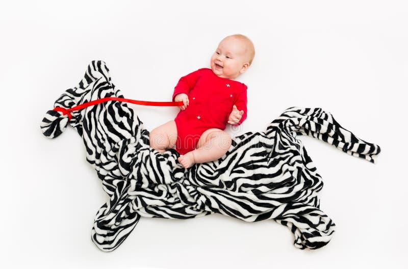 一个四个月孩子在地板乘坐从布料的一匹斑马 库存照片