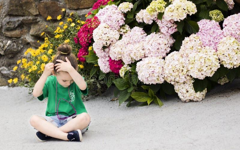 一个四岁的女孩在她的头发安置万寿菊花 图库摄影
