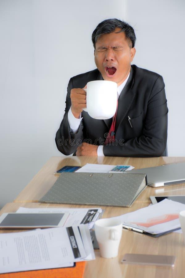 一个困疲乏的亚洲商人的画象打瞌睡和喝咖啡在工作地点/孤立 库存图片