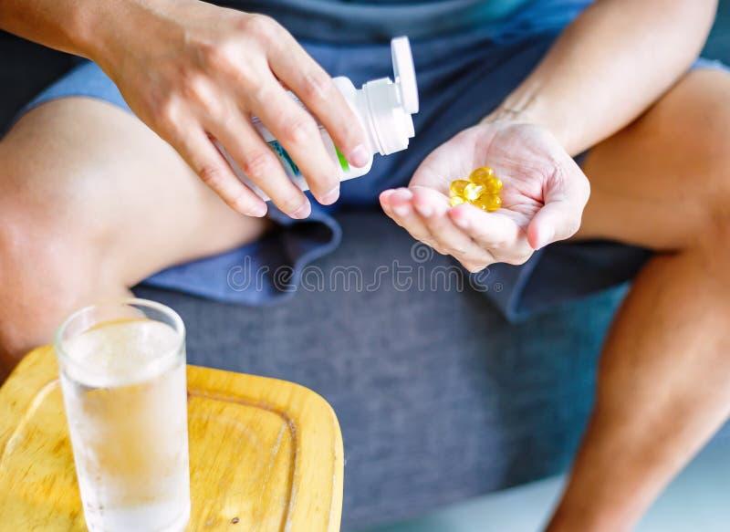 一个圆的黄色药片照片在手中 人采取与杯的医学水 维生素,有效的药物的每日准则, 免版税库存图片