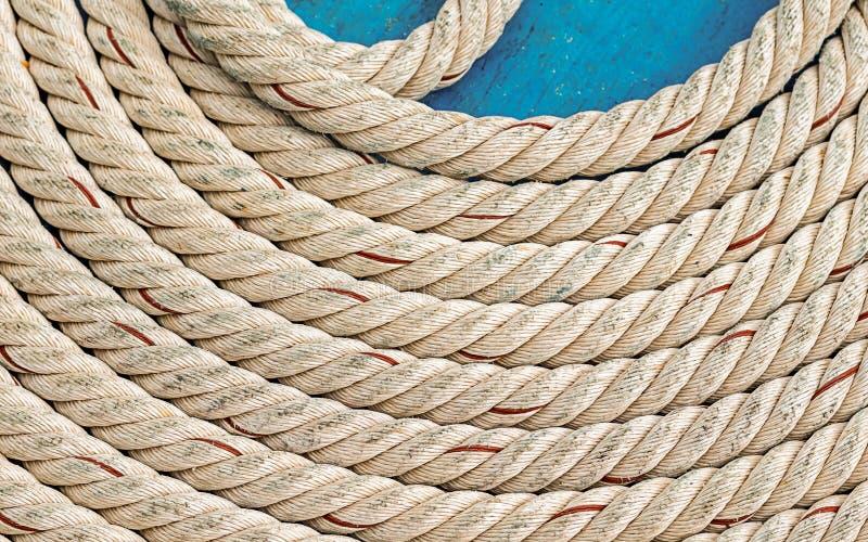 一个圈子的白色厚实的绳索圈子零件在蓝色甲板背景海洋紧固件的 免版税图库摄影