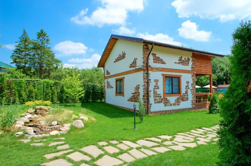 一个土气样式的两层乡间别墅在夏天庭院里站立.图片
