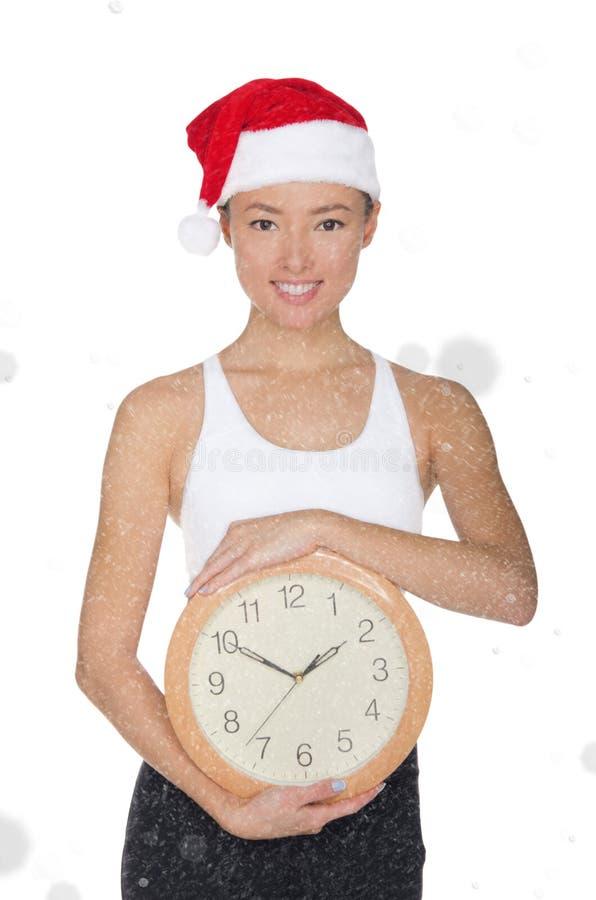 一个圣诞老人` s帽子的亚裔妇女有时钟的 免版税库存照片