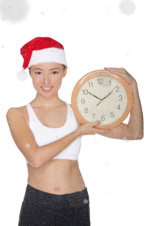 一个圣诞老人` s帽子的微笑的亚裔妇女有时钟的 库存照片