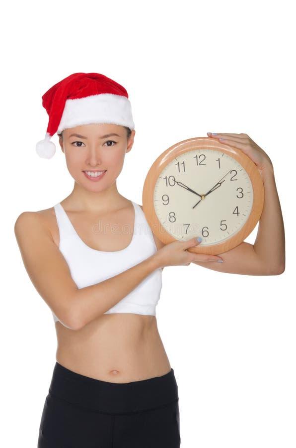 一个圣诞老人` s帽子的愉快的亚裔妇女有时钟的 免版税库存照片