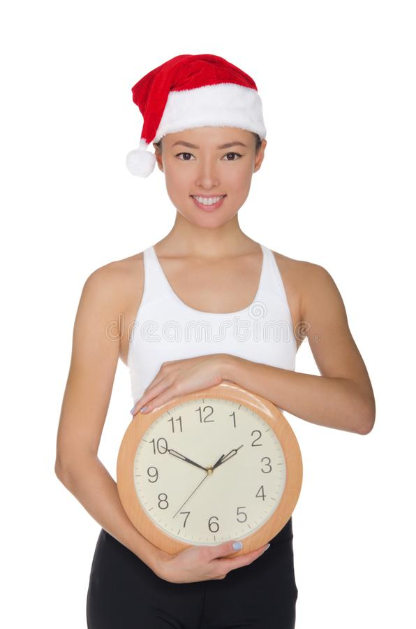 一个圣诞老人` s帽子的美丽的亚裔妇女有时钟的 免版税库存照片