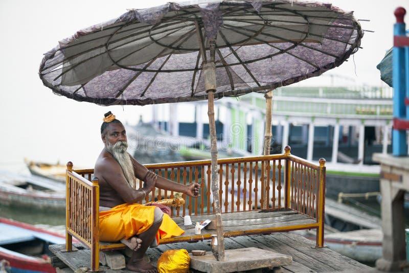 一个圣洁者, sadhu坐瓦腊纳西的堤防,在一把伞下在清早 库存图片