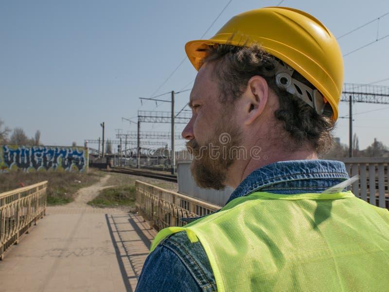 一个在一件盔甲的人和髭的画象有胡子的以铁路轨道为背景 铁路工作者 免版税库存图片