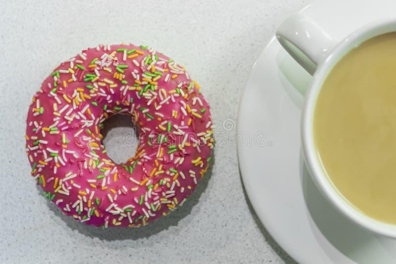 一个在我旁边的多福饼明亮的色的谎言与一杯咖啡wi 库存照片
