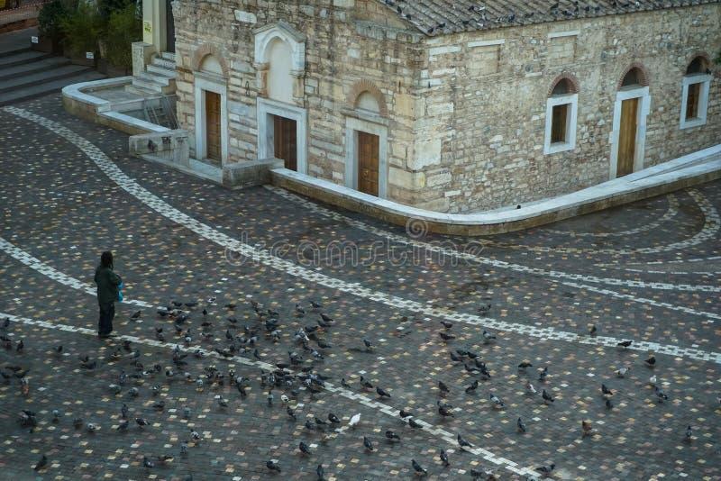 一个在美好的地板样式Monastiraki广场的人哺养的鸽子在古老教堂前面早晨 免版税库存图片