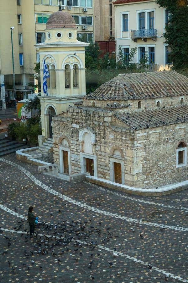 一个在美好的Monastiraki广场的人哺养的鸽子在古老Pantanassa教堂前面早晨 免版税库存照片