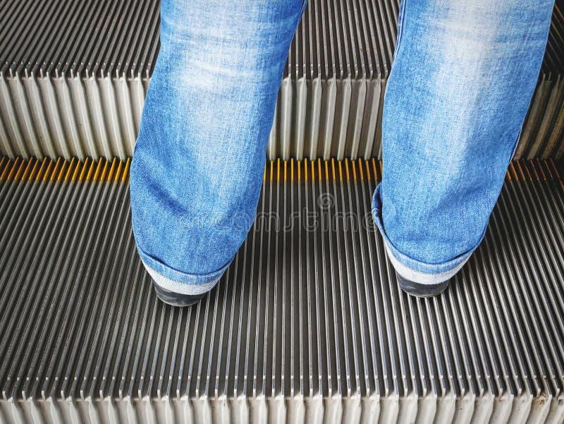 一个在自动扶梯的人佩带的蓝色牛仔裤的特写镜头更低的部分后面看法  库存照片