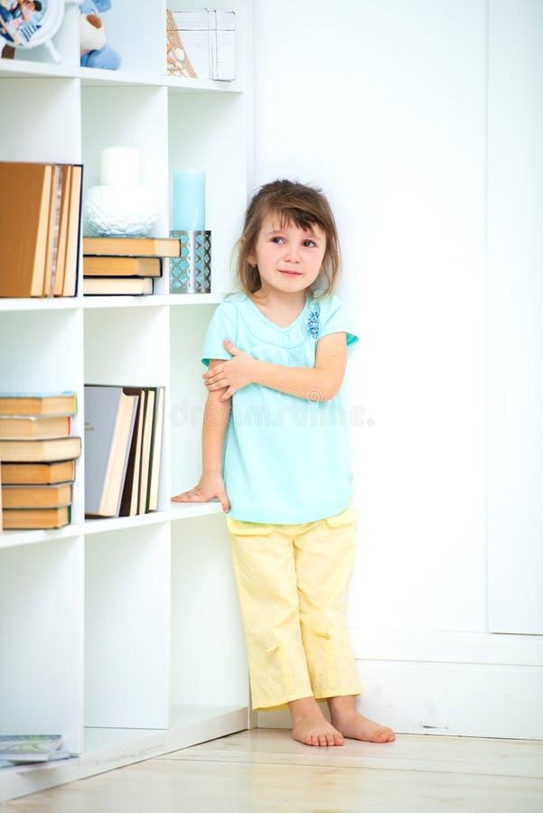 一个在角落惩罚的哀伤的矮小的欠债女孩立场 孩子的酒和处罚 库存图片