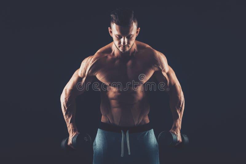 一个在dar的肌肉年轻人举的哑铃重量的特写镜头 图库摄影