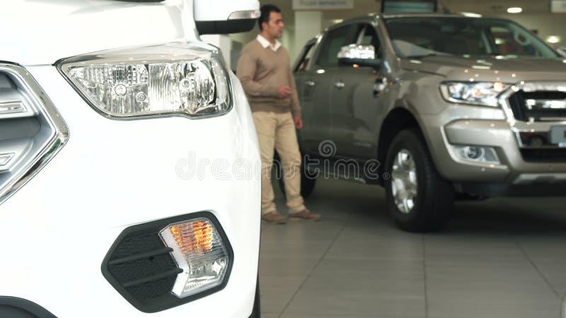 一个坚实人在汽车中走在售车行 免版税库存图片