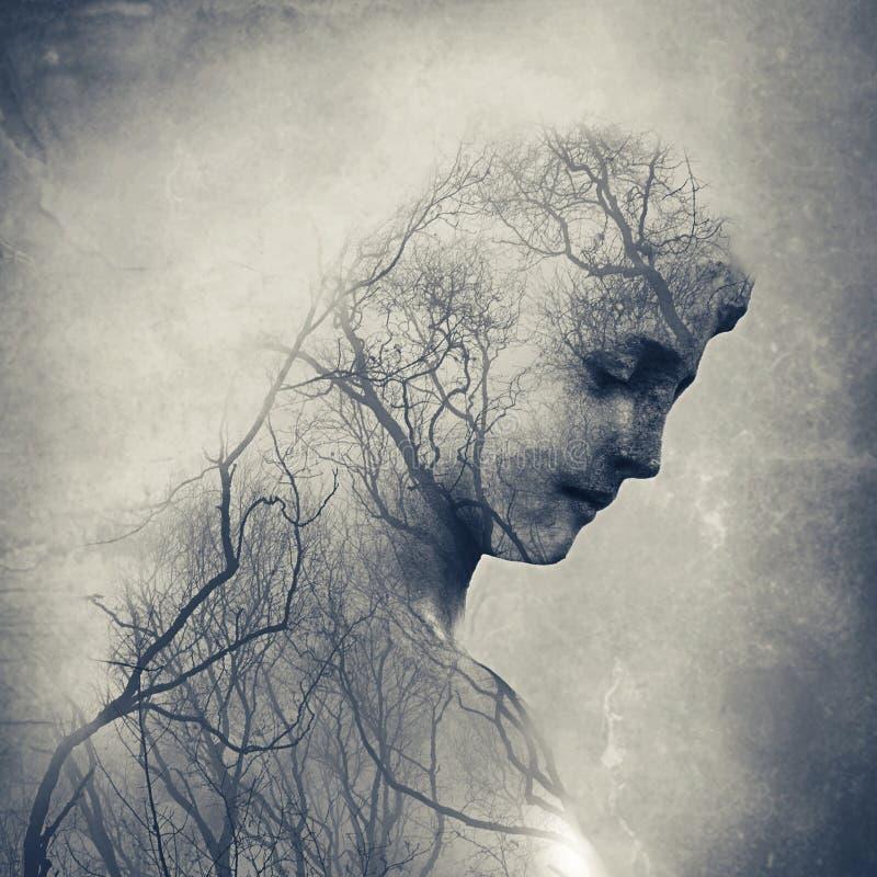 一个坟园天使的两次曝光与冬天包括她的面孔和身体的树枝的 库存图片