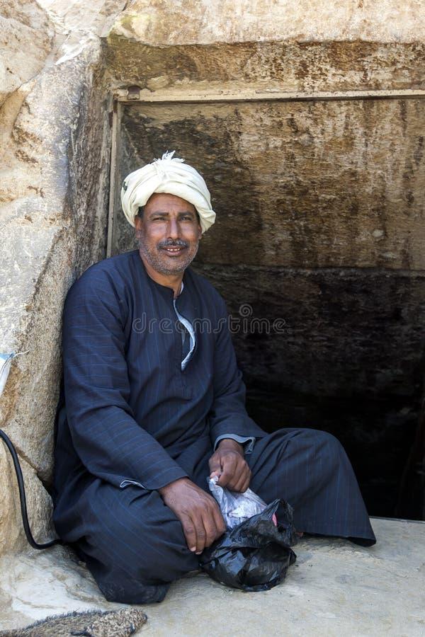 一个埃及人坐在入口到在红色金字塔里面的一个隧道在埃及 免版税库存图片