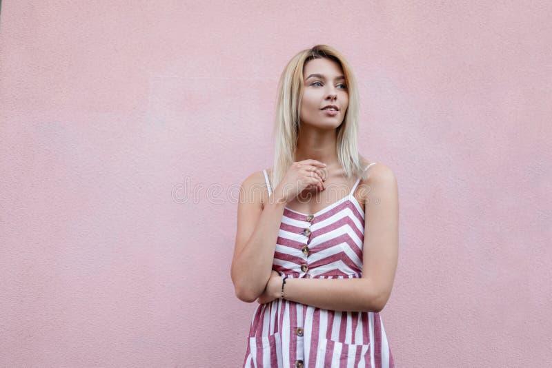 一个夏天时髦的镶边sundress的可爱的年轻白肤金发的妇女在桃红色葡萄酒墙壁附近休息在城市 美丽的逗人喜爱的女孩 库存照片