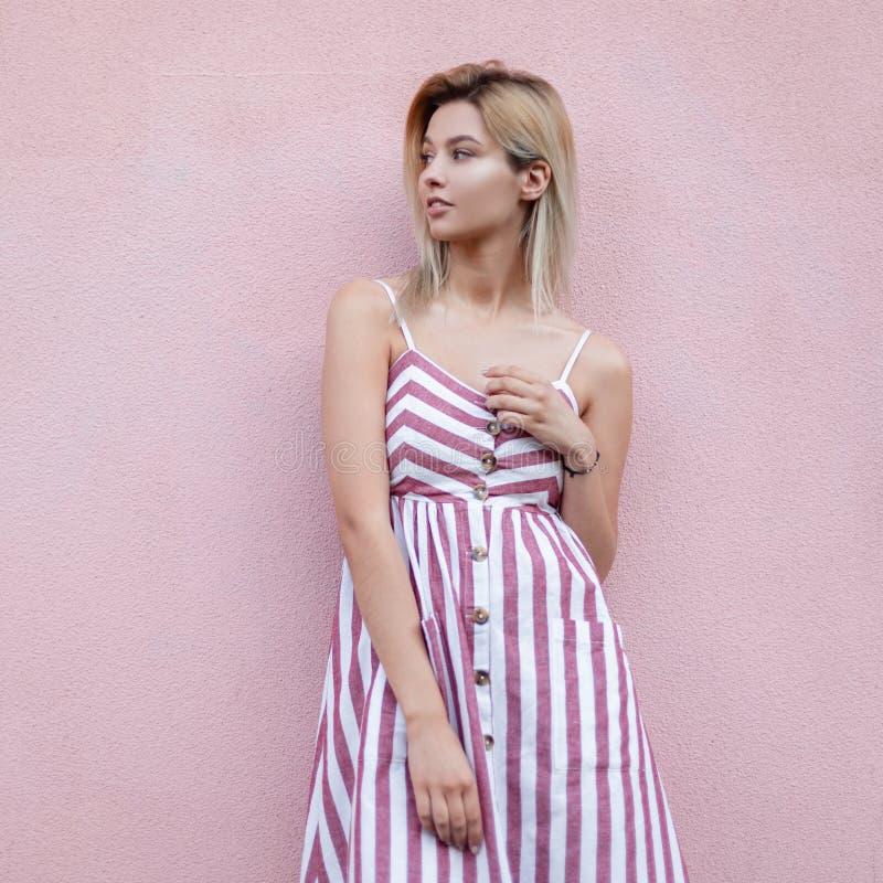 一个夏天时髦的镶边sundress的欧洲俏丽的年轻白肤金发的妇女在桃红色葡萄酒墙壁附近休息在城市 免版税图库摄影
