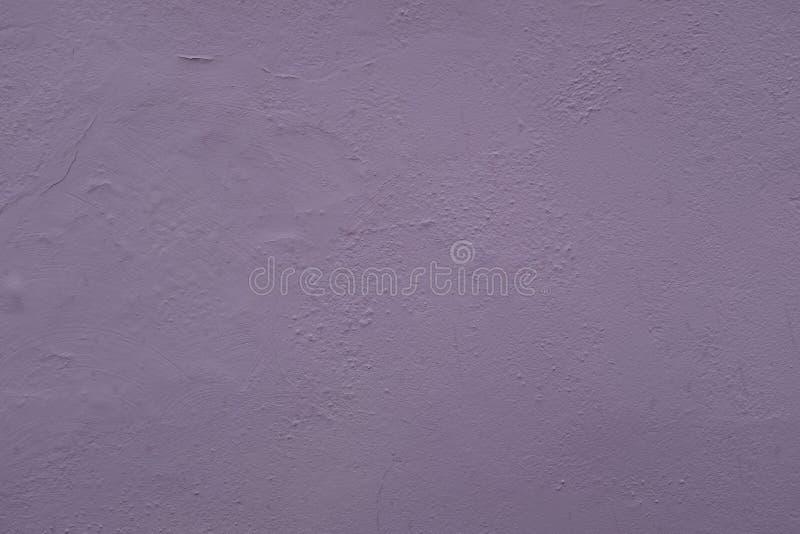 一个外墙的照片的关闭绘了紫色构造,与灰泥涂抹的表面,伟大为背景 免版税库存图片