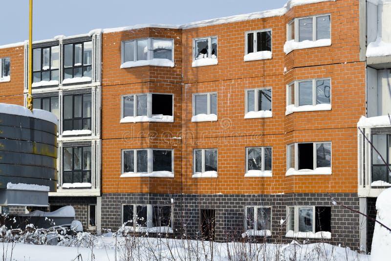 一个多层的大厦的被放弃的建筑 塔吊和一个房子有残破的玻璃的 冬天 俄国 库存照片