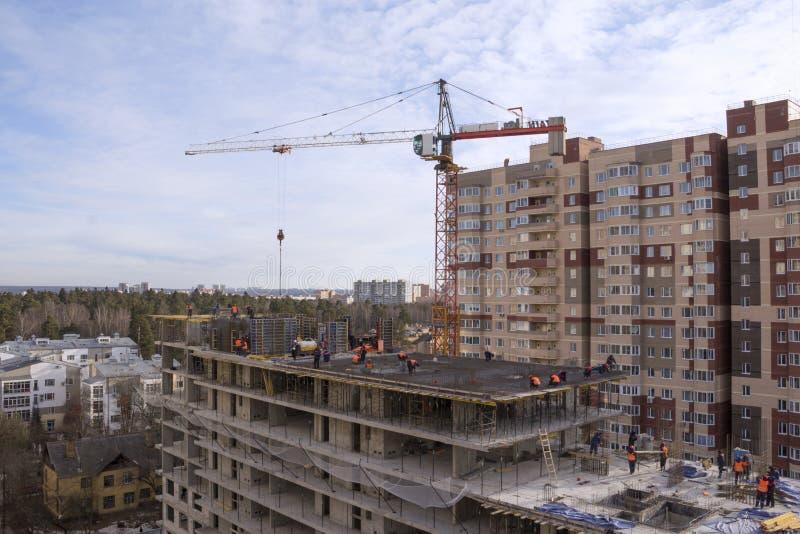 一个多层的大厦,在工地工作的一台起重机的建筑 库存图片