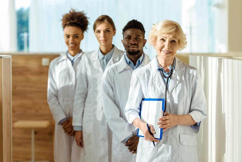 一个多种族小组医生在实验室涂上身分 免版税库存图片