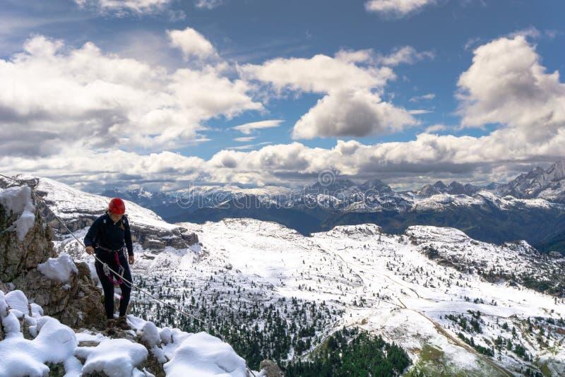 一个多雪和被暴露的土坎的女性登山人在白云岩 免版税图库摄影