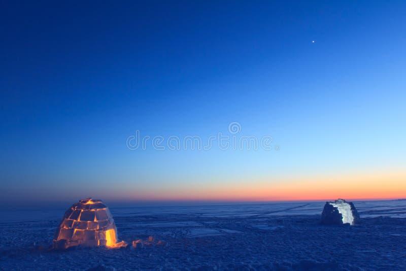 一个多雪的房子叫园屋顶的小屋在日落 图库摄影