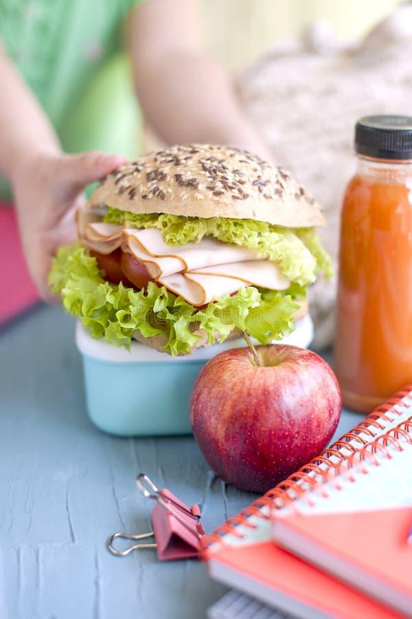 一个大三明治在女小学生的手上 学校笔记本和午餐 安置文本 去学校 免版税库存照片