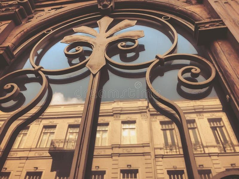 一个大厦的反射在街道上的在与铁装饰装饰品的玻璃木门 老第比利斯建筑学 免版税库存照片
