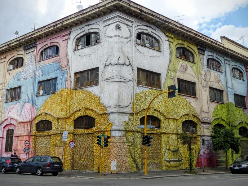 一个大厦的街道艺术与罗马Ostiense区的色的恶魔般面孔的在意大利 免版税库存照片
