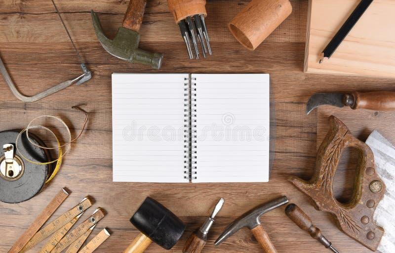 一个大小组的大角度特写镜头在与空白页的一个开放笔记本附近被安排的工具 库存照片