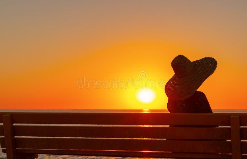一个大帽子的妇女坐长凳和神色在日落 图库摄影