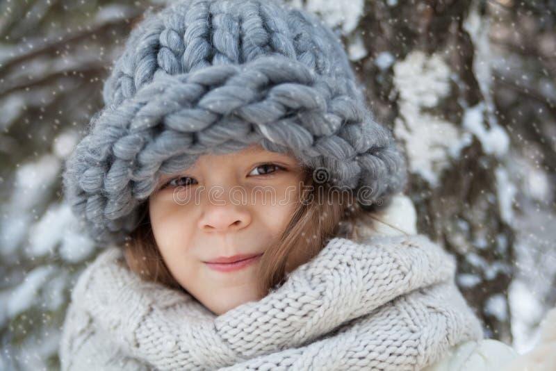 一个大帽子的小女孩在冬天画象 免版税图库摄影