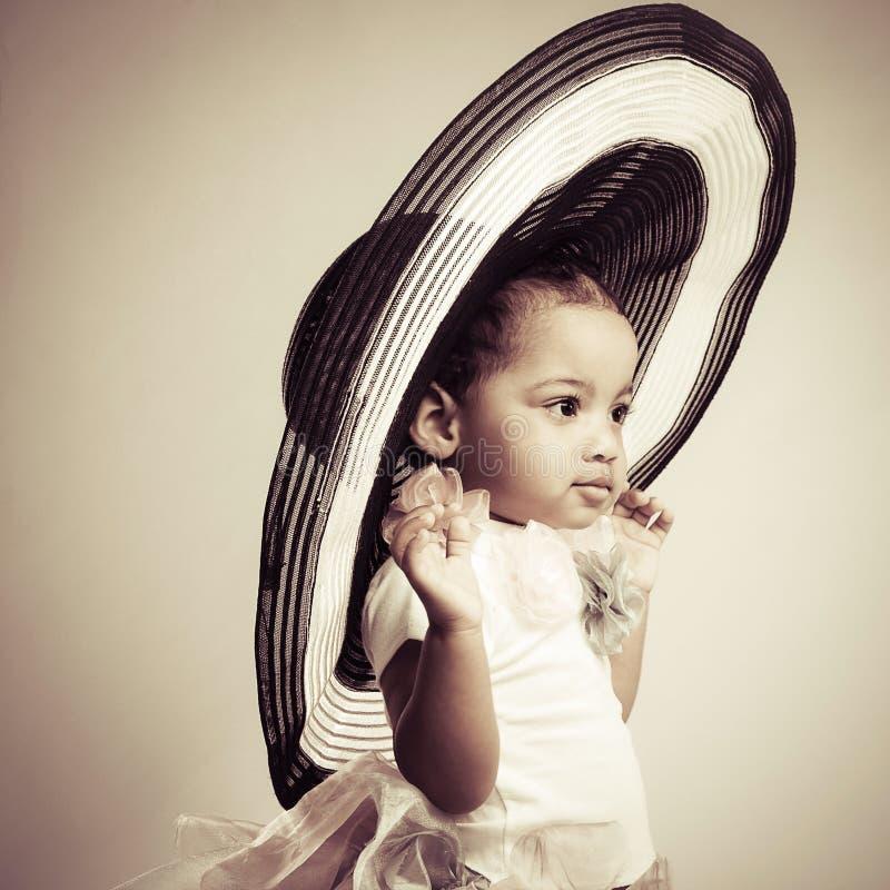 一个大时兴的帽子的可爱的小女孩 免版税库存图片