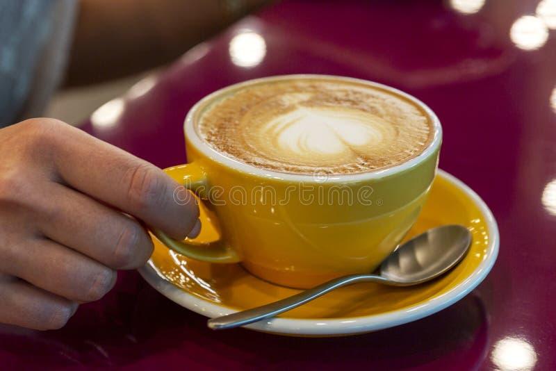 一个大杯子与心脏的热奶咖啡在皮肤在坐在餐馆的女孩的手上 r 免版税图库摄影