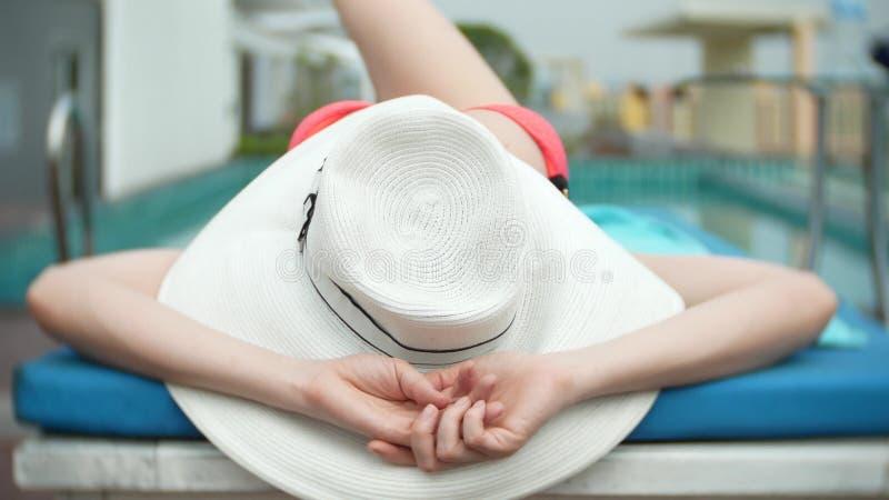 一个大白色帽子和桃红色比基尼泳装的一名无法认出的亭亭玉立的大乳房妇女在轻便马车休息室说谎在水池附近 她 免版税库存图片