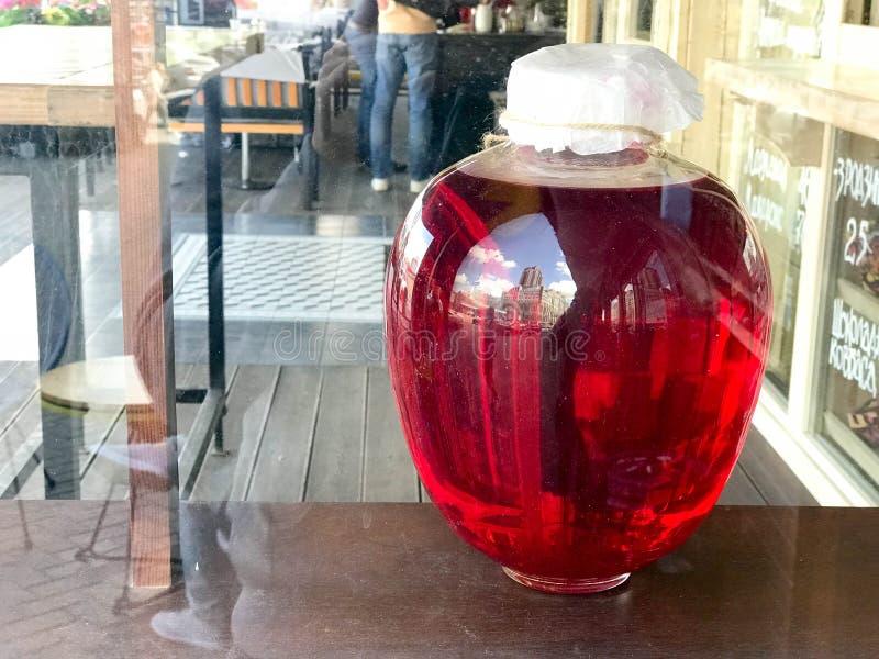 一个大红色透明玻璃圆的光亮明亮的瓶子,可口甜汁液,篮的容量,平均观测距离,酒,液体s 免版税库存照片