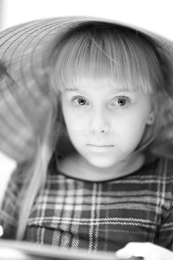 一个大草帽的一个逗人喜爱的白肤金发的女孩 免版税库存照片