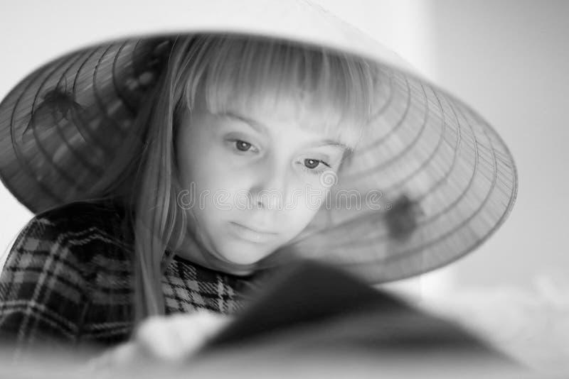 一个大草帽的一个逗人喜爱的白肤金发的女孩 库存照片