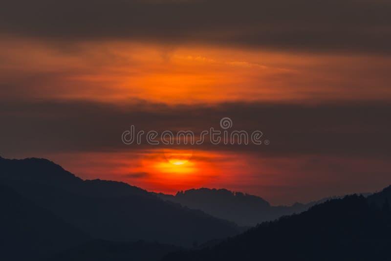 一个大落日的美好的风景在山的剪影的 库存图片
