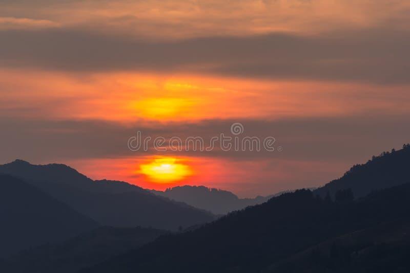 一个大落日的美好的风景在山的剪影的 库存照片