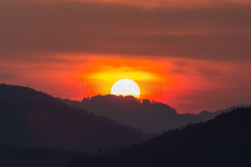 一个大落日的美好的风景在山的剪影的 图库摄影