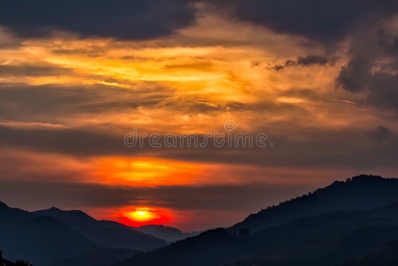 一个大落日的美好的风景在山的剪影的 免版税库存照片