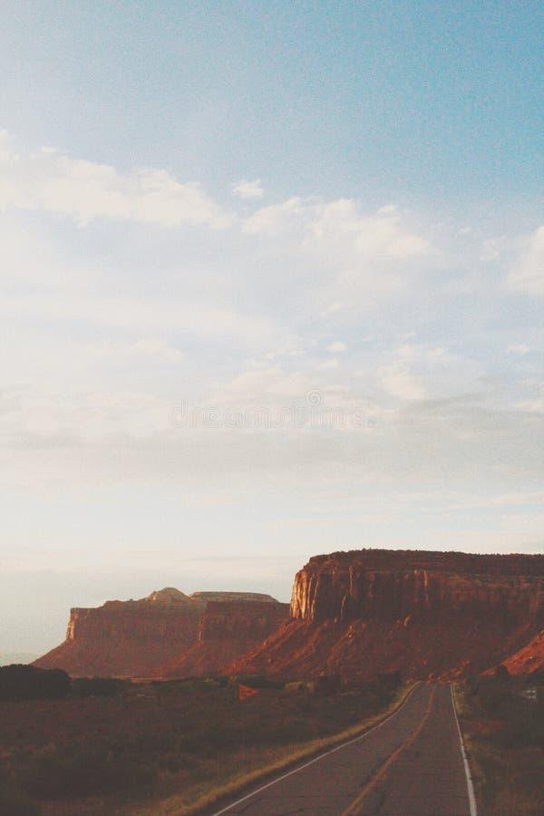一个大高原的美丽的垂直的射击在白色云彩下的一片沙漠在Canyonlands 图库摄影